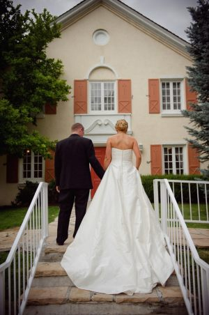 Bride and groom on steps ~ Photo by Dezember Photography